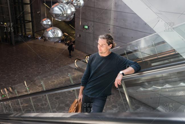 Malmo, Sweden - June 9, 2016: Man leisurely riding escalator