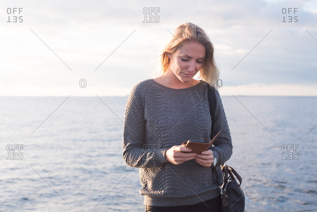 Woman on sunny shore checking phone