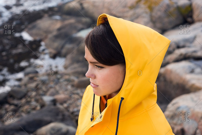 Woman in raincoat on shore
