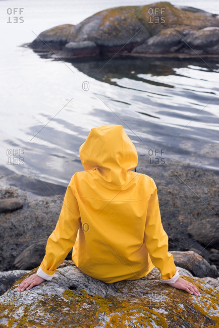 Woman sitting on shore in raincoat
