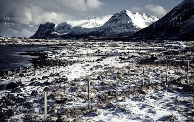 Snowy field of rocks near a waterway in Lofoten, Norway