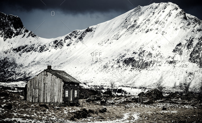 Wooden cabin at the base of a frozen mountain in Lofoten, Norway