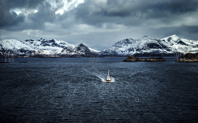 Trawling boat gliding through the water in an arctic bay
