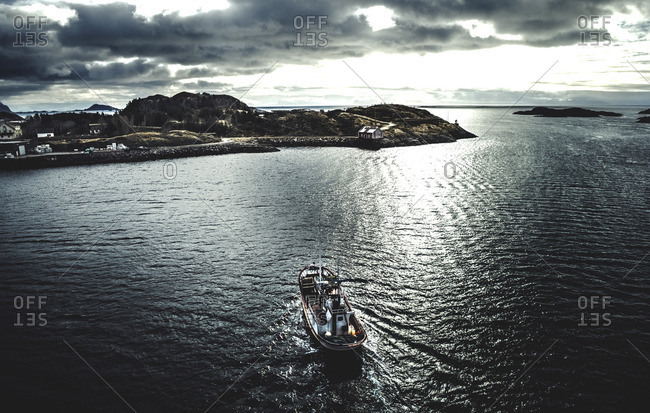 Trawling boat gliding through the water in an arctic bay toward a village