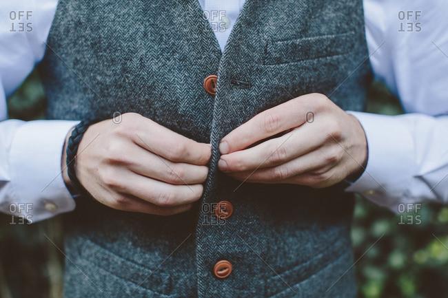 Man buttoning formal vest