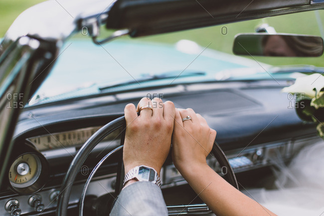 Hands of newlyweds in car