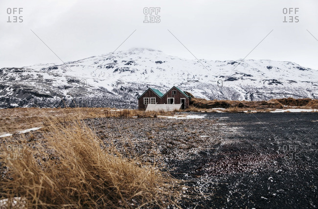 Cabin in field with snow-covered hills