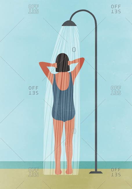 Rear view of woman having outdoor shower at beach