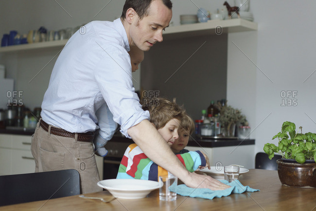 Father carrying toddler wiping table while children having food at kitchen