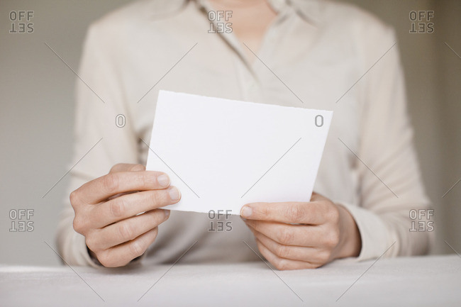 Midsection of mid adult woman holding a blank card