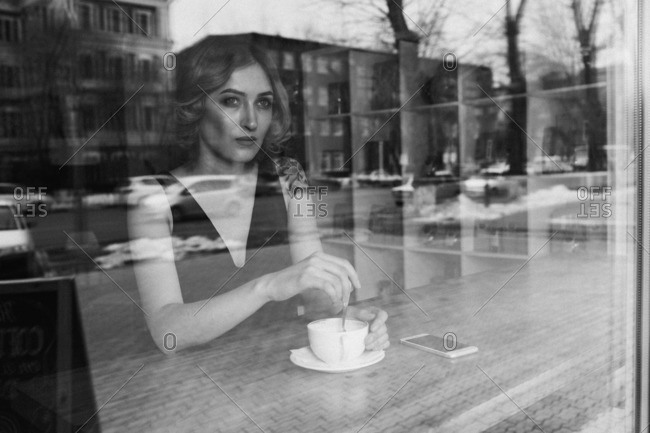 Thoughtful young woman stirring coffee in coffee shop