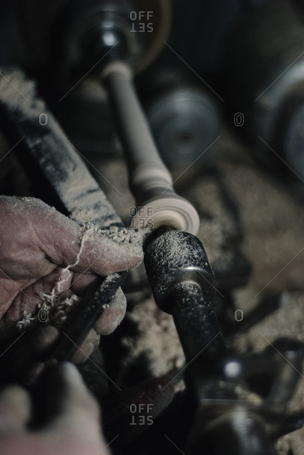 Cropped image of craftsman hands using wood lathe for making flute at workshop