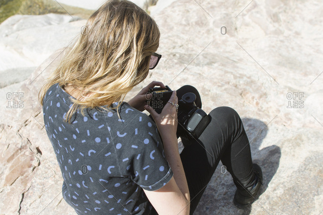 Woman loads film camera while sitting on rock
