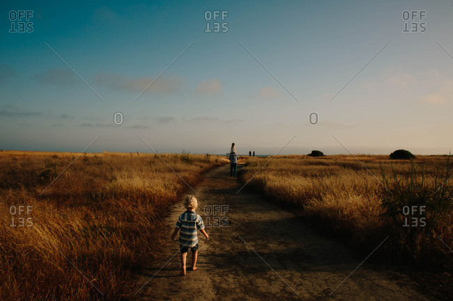 Boy follows his father and sister down path at dusk