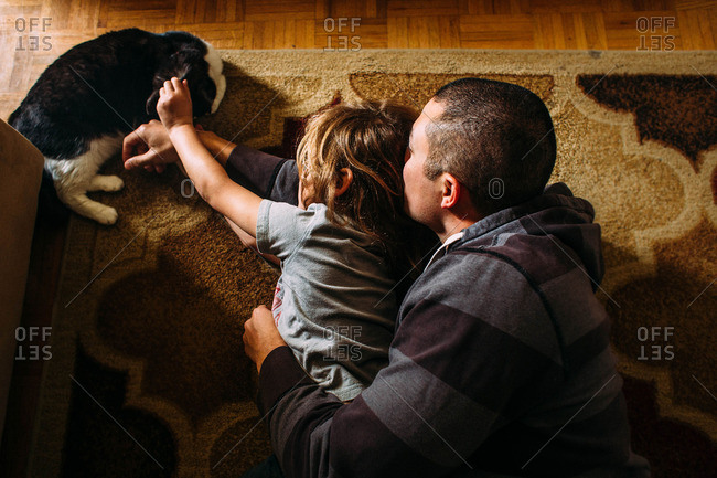 Father and child lying on rug with cat