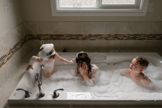 Elevated view of three young children playing in bubble bath stock ...