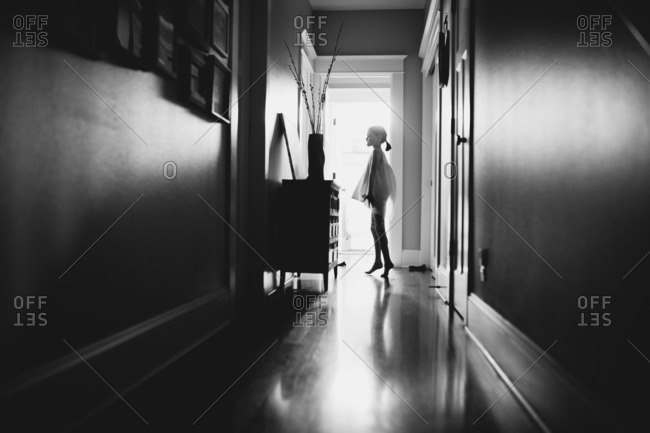 Girl silhouetted in hallway on tiptoes