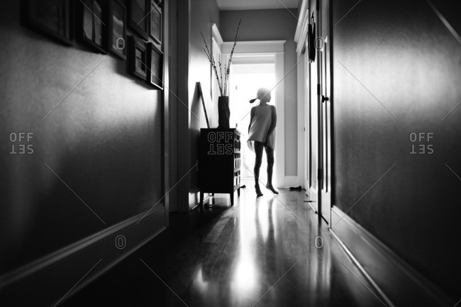 Young girl silhouetted in hallway