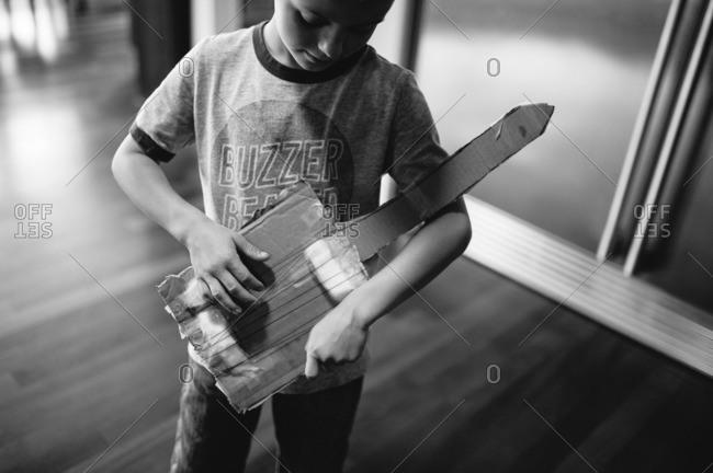 Boy playing a cardboard guitar