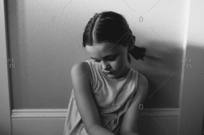 Portrait of pensive young girl sitting against wall