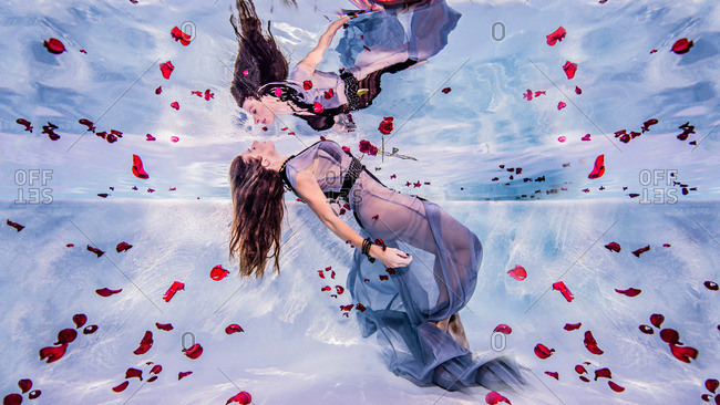Woman underwater with rose petals