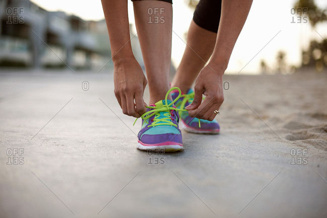 Low section of woman wearing training shoes tying shoelace
