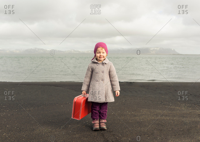 Portrait of young girl holding red suitcase
