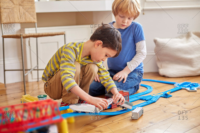 Two young boys playing with toy train set