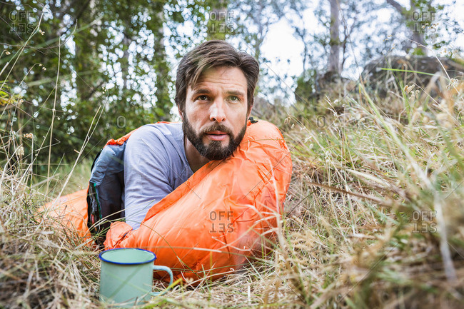 Man watching from sleeping bag in forest