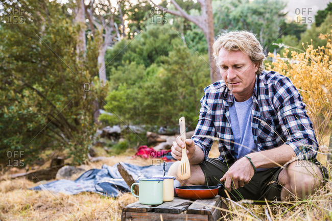 Mature man frying breakfast on camping stove in forest