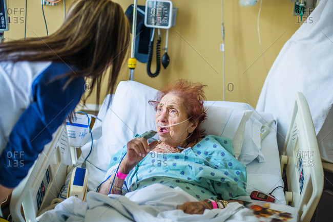 Senior patient on hospital bed talking to visitor