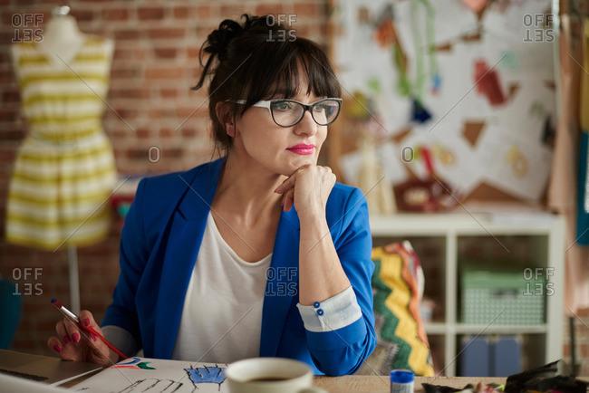 Woman in design studio, hand on chin, looking away