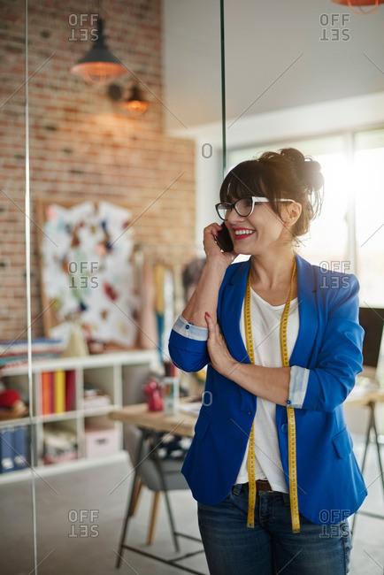 Woman in design studio making telephone call looking away smiling