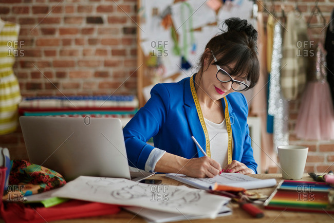Woman in design studio sitting at desk sketching fashion design