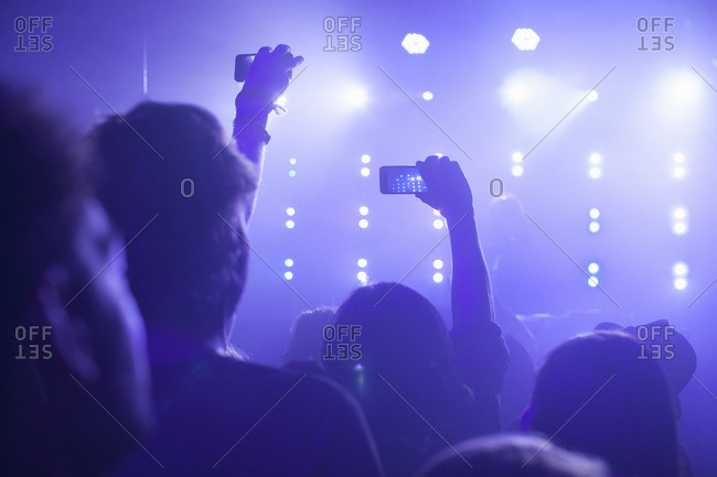 Rear view of group in club arms raised filming concert on smartphone