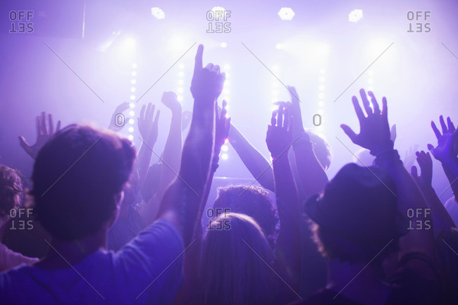 Rear view of group in club arms raised watching concert