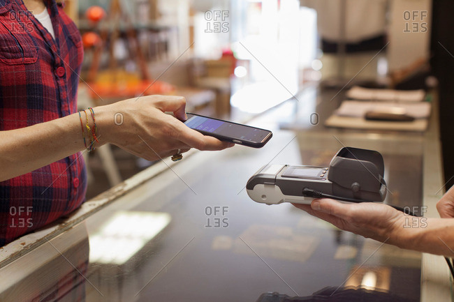 Woman's hands using smartphone to make contactless payment on smartphone