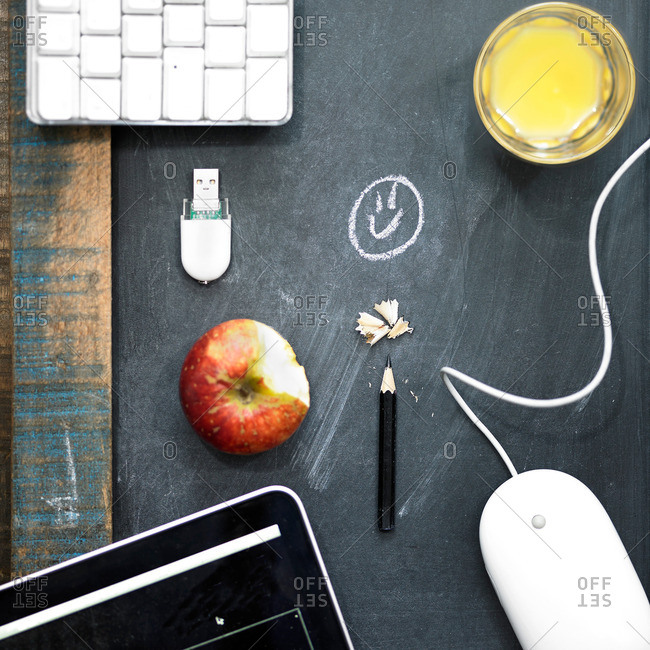 Overhead view computer equipment, apple and orange juice on blackboard surface