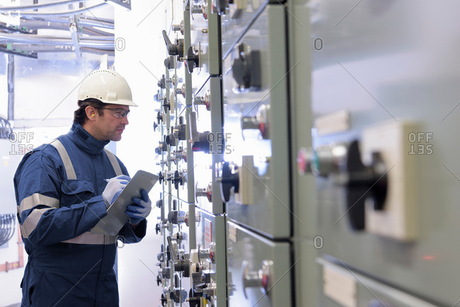 Worker inspecting switch gear in hydroelectric power station