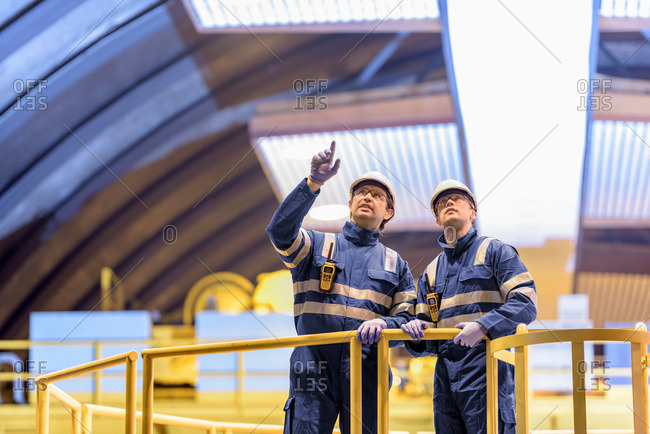 Worker explaining things to another in a generating hall in hydroelectric power station