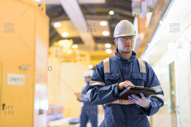 Portrait of worker in generating hall in hydroelectric power station with a tablet