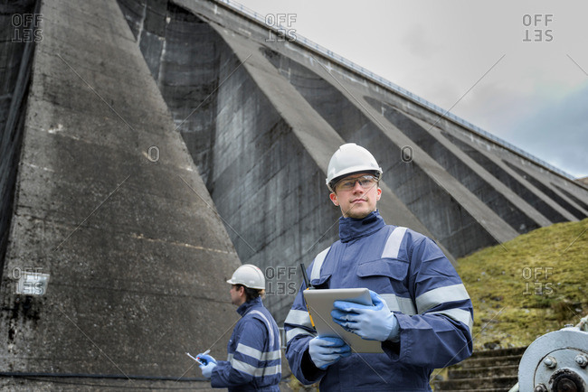 Portrait of worker at foot of dam at hydroelectric power station