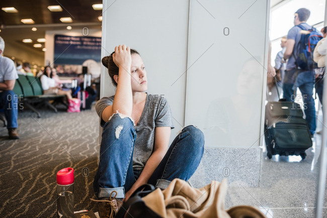 Fed up young woman sitting on airport floor