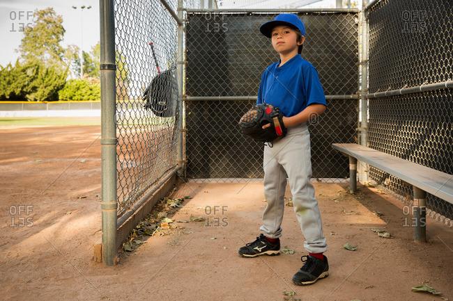 Portrait of boy wearing baseball glove at baseball practice