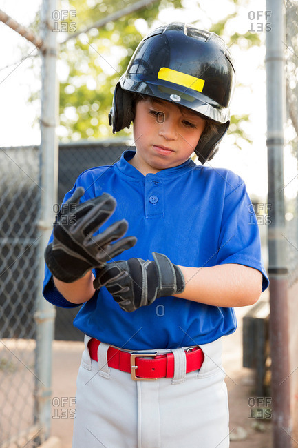 Boy putting on baseball gloves at baseball field