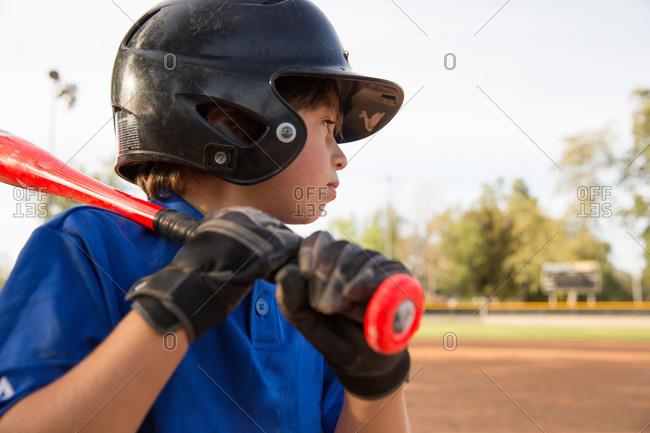 Close up of boy preparing to bat at practice on baseball field