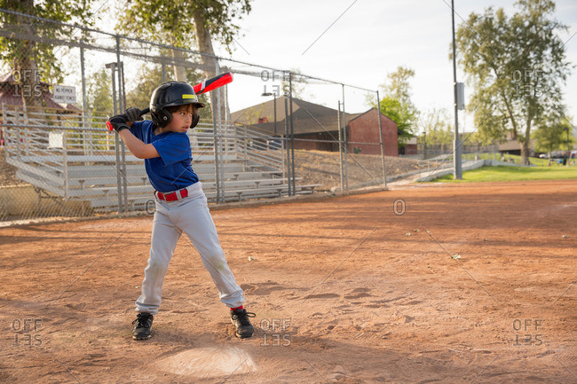 Boy batting at practice on baseball field