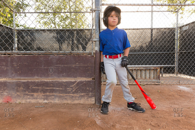Boy leaning against fence with baseball bat at practice on baseball field