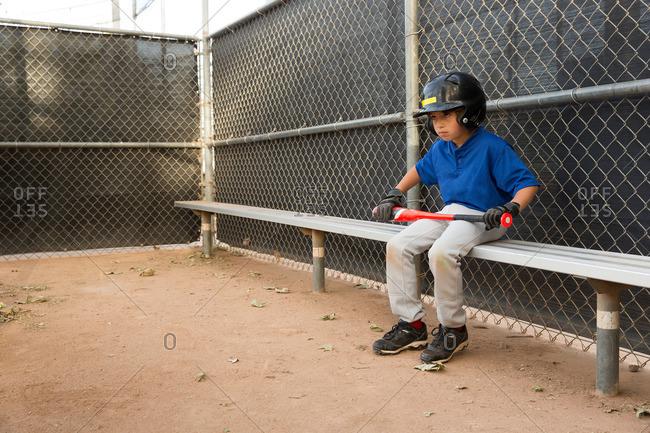 Boy with baseball sitting on bench at baseball practice