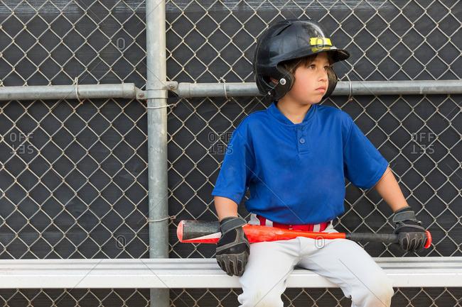 Boy with baseball bat watching from bench at baseball practice